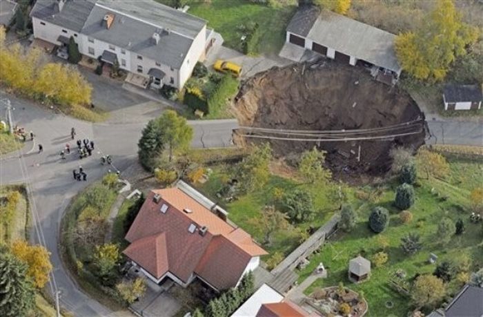 In this aerial photo, a giant landslide under a residential street which claimed a car and left another car hanging over the edge is seen in Schmalkalden, central Germany, Monday, Nov. 1, 2010. The cause of the landslide is yet unclear unclear. Residents were evacuated from 23 buildings. Nobody was injured. (AP Photo/Jens Meyer)