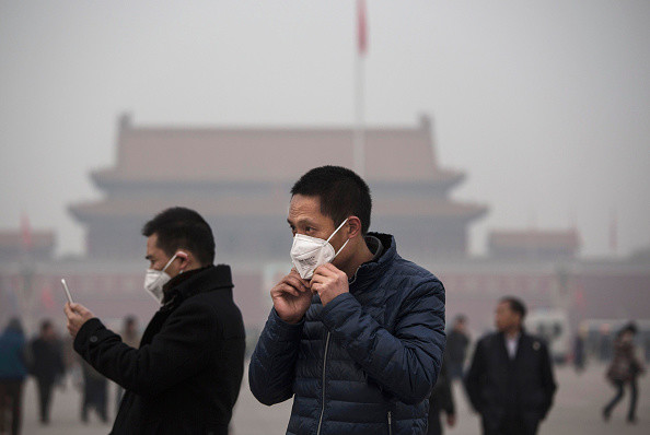 "BEIJING, CHINA - DECEMBER 09: A  tourist puts on a face mask to protect against pollution as he visits Tiananmen Square during smog in Tiananmen Square on December 9, 2015 in Beijing, China. The Beijing government issued a ""red alert"" Sunday for the first time since new standards were introduced earlier this year as the city and many parts of northern China were shrouded in heavy pollution. Levels of PM 2.5, considered the most hazardous, crossed 400 units in Beijing, lower then last week, but still nearly 20 times the acceptable standard set by the World Health Organization. The governments of more than 190 countries are meeting in Paris to set targets on reducing carbon emissions in an attempt to forge a new global agreement on climate change.  (Photo by Kevin Frayer/Getty Images)"