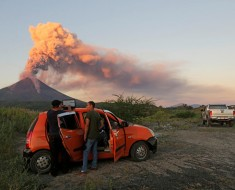 People look at the Momotombo volcano erupting in Papalonal community in La Paz Centro, Leon, Nicaragua on December 2, 2015. A large volcano in western Nicaragua, Momotombo, on Tuesday belched ash and gas up to a kilometer (3,000 feet) in the sky, sparking fears that the giant could be waking from a fitful 110-year-old slumber. AFP PHOTO/ STR / AFP / STR        (Photo credit should read STR/AFP/Getty Images)